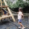 Girl walking across rope bridge on wooden playground