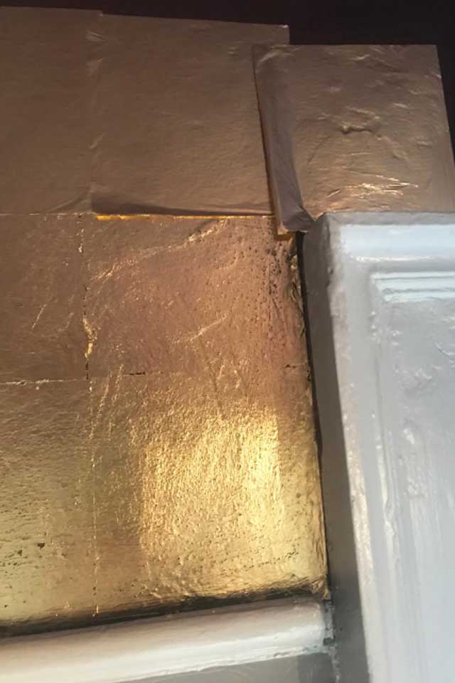 gold leaf being applied to ceiling in small wedding venue