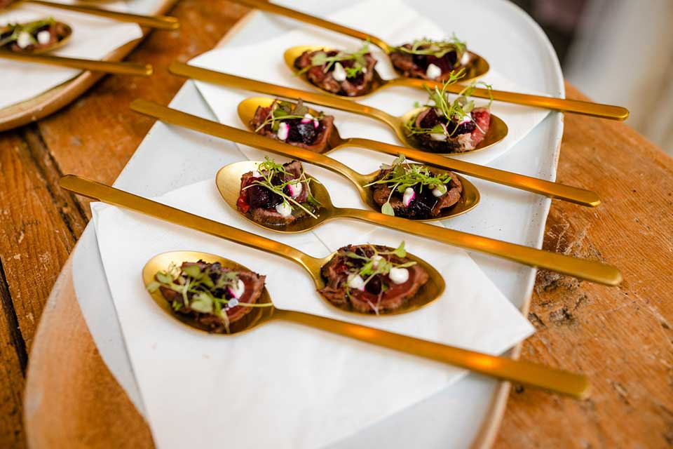 gold spoons resting on plate with delicate canapes in centre