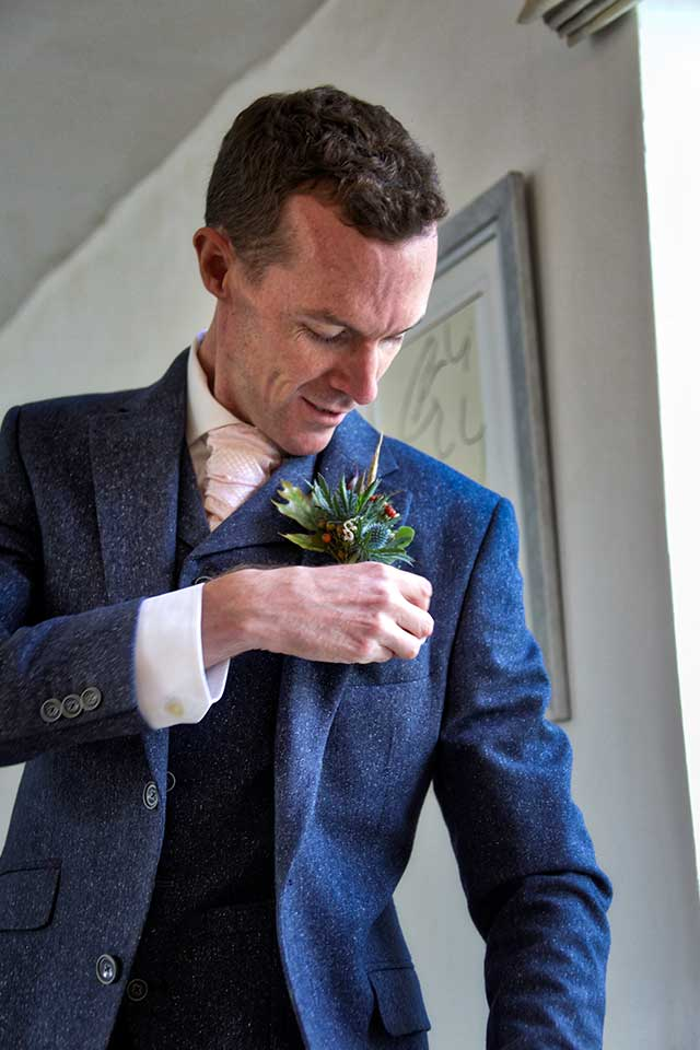 groom in navy suit fastening buttonhole