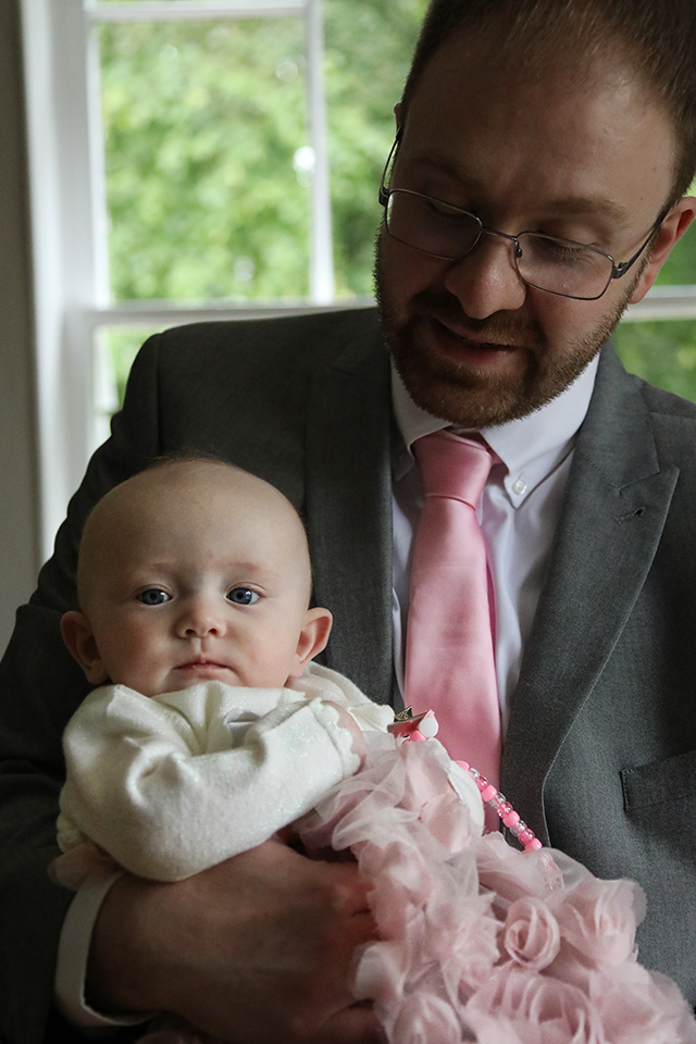 groom holding baby girl on wedding day