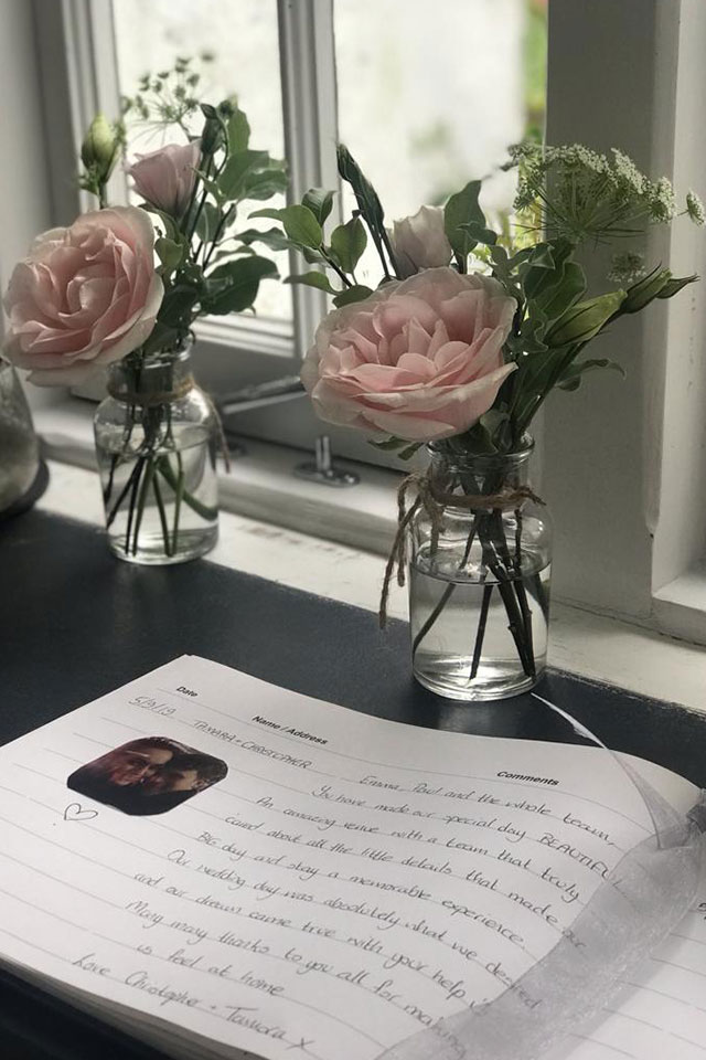 open wedding guest book with pink flowers in vase