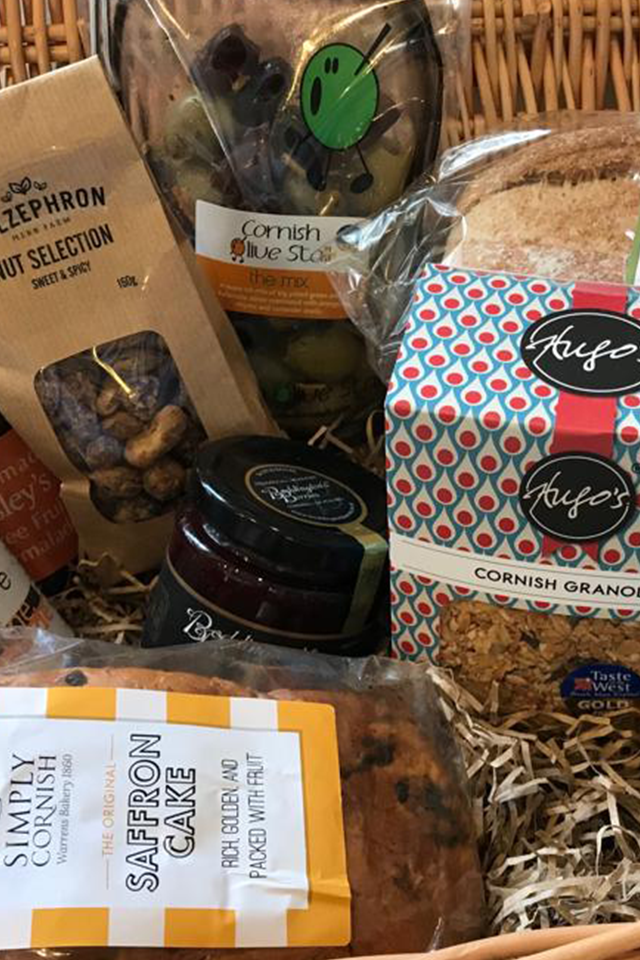 Contents of a Cornish welcome hamper with saffrom cake, fresh preserves and Cornish granola