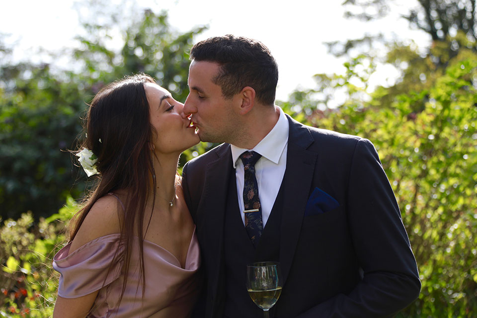 happy wedding guests kissing in sunshine