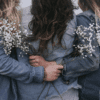 3 women embracing with white flowers