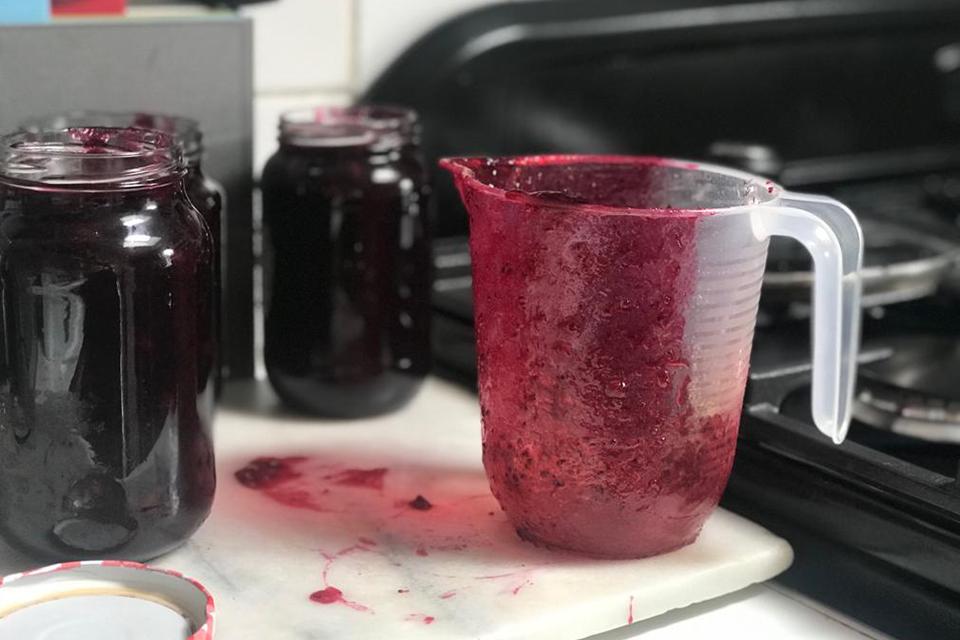 Plastic jug covered in homemade jam pouring into jam jars