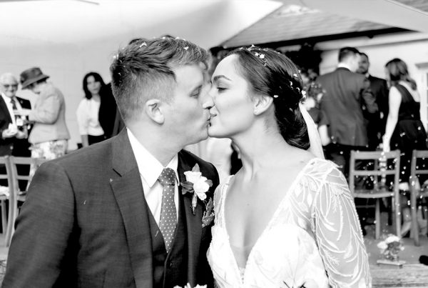 black and white image of bride and groom kissing