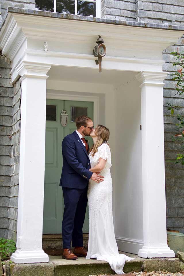 bride and groom kissing outside Georgian house