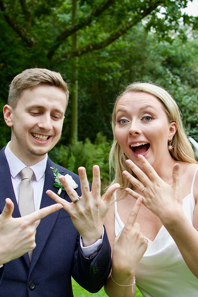 smiling bride and groom pointing at wedding rings