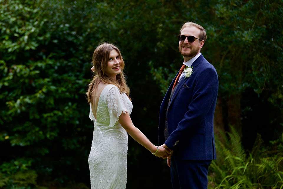 bride and groom holding hands in garden