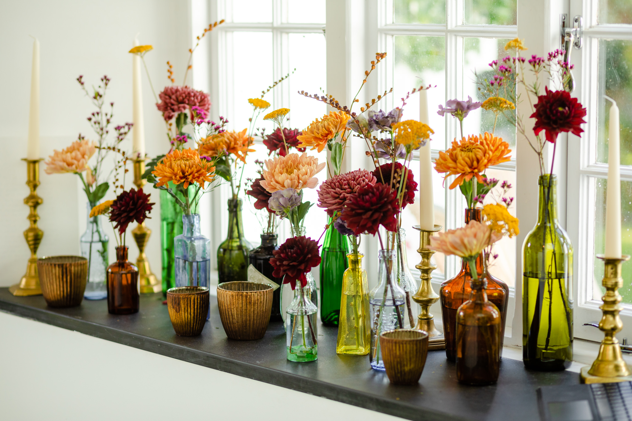 colourful glass bottles with autumn flowers on windowsill