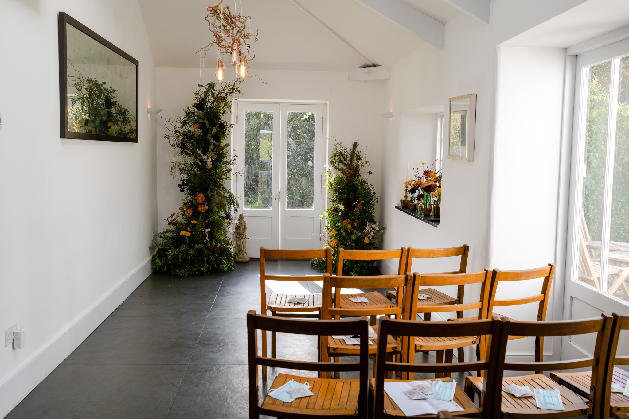 small wedding ceremony setup with wooden chairs and floral installation