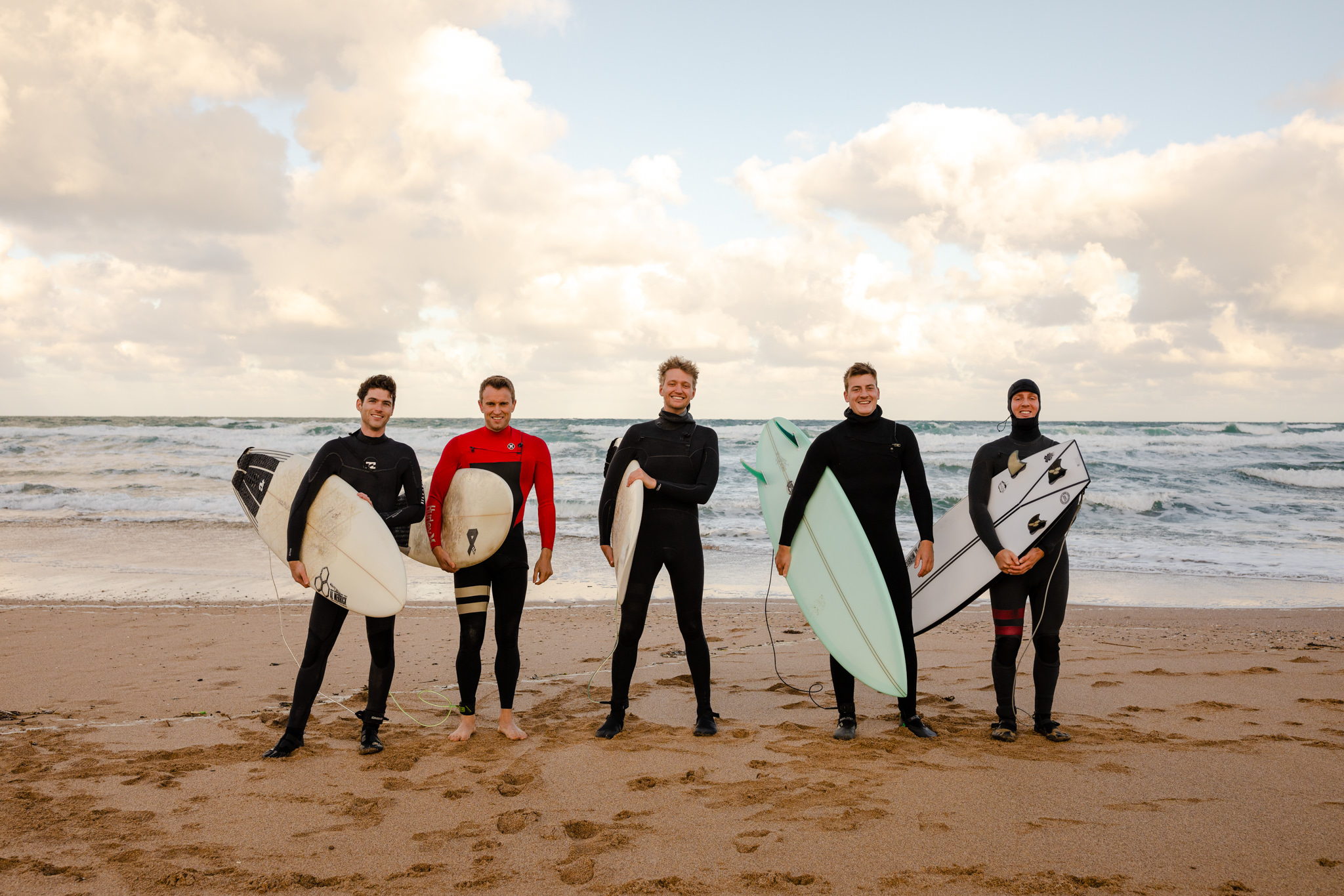 5 men wearing wetsuits standing on the beach carrying surfboards