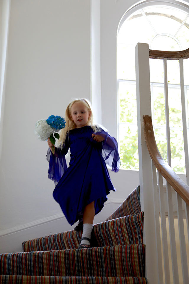 young bridesmaid walking down stairs with flowers