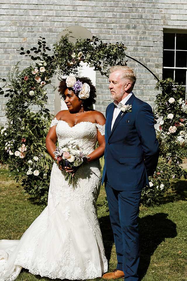 elopement wedding couple stood in garden under floral arch