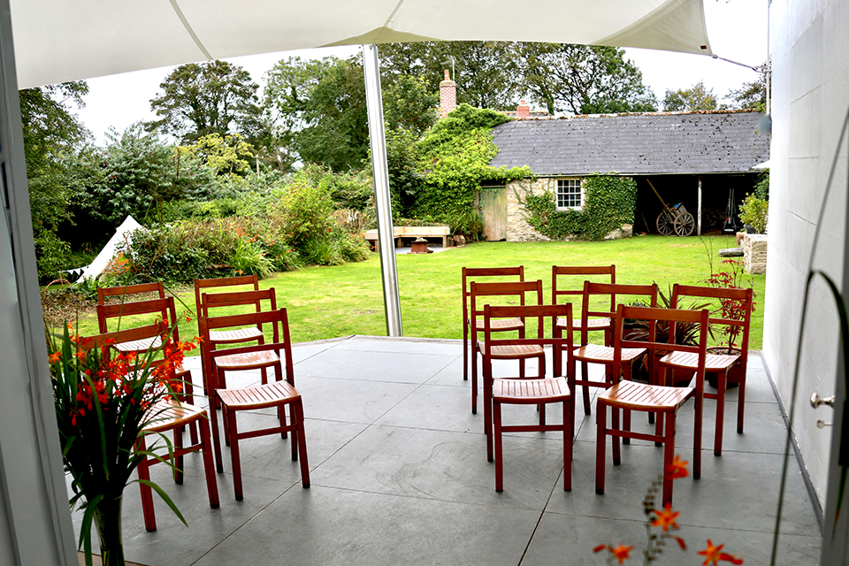 Vintage wooden chairs setup for outdoor small wedding ceremony under canopy in country house garden