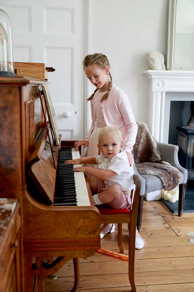 little boy sat at Bechstein Piano in small wedding venue with girl standing next to him