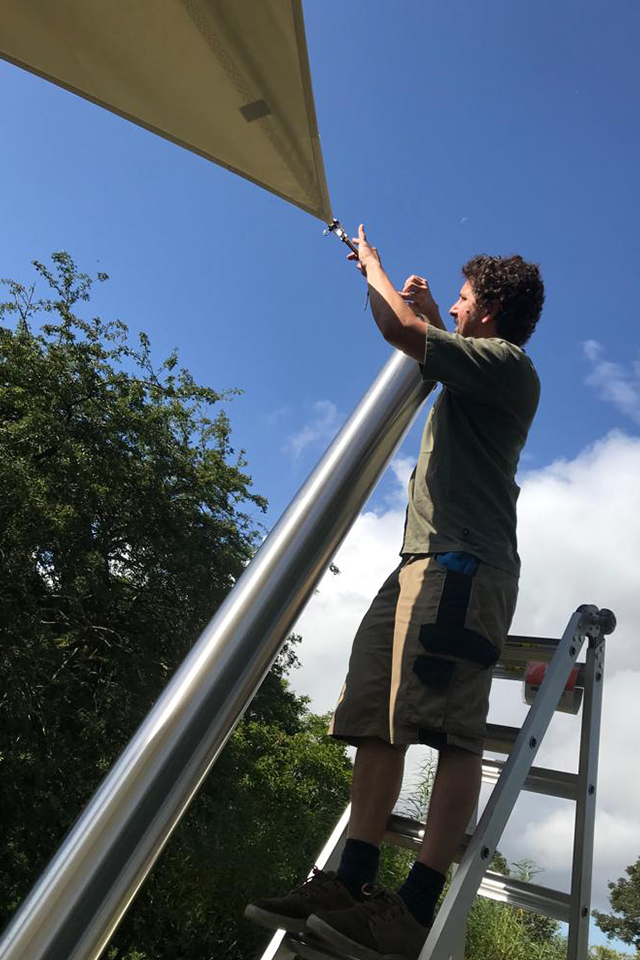 Man under blue sky putting up bespoke shade sail canopy