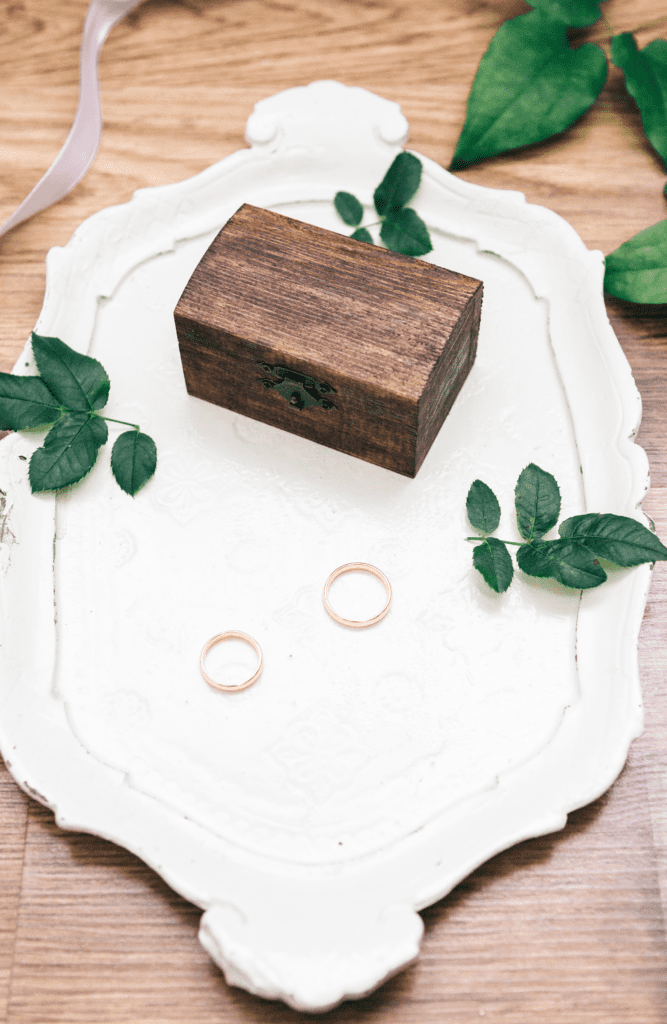 gold wedding rings on white plate with wooden box