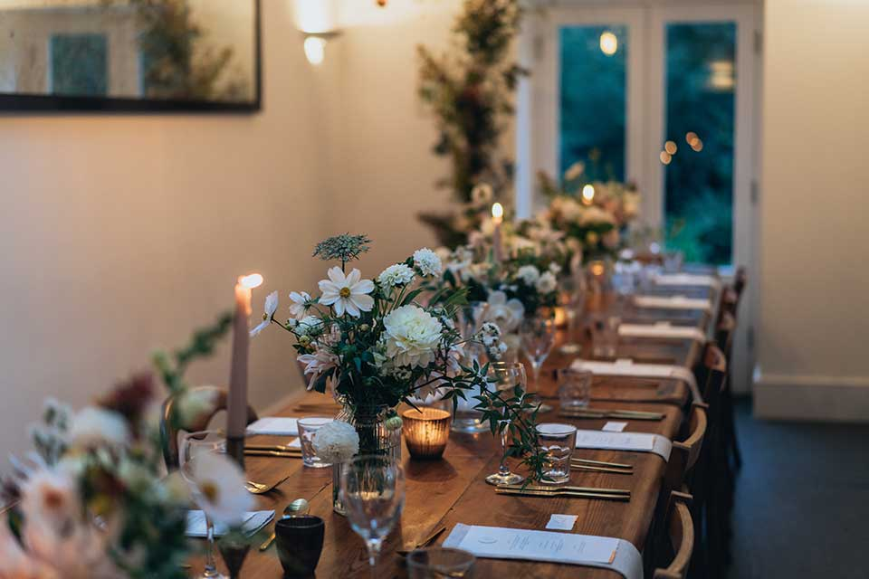 Intimate small wedding table setting with fresh flowers and candles