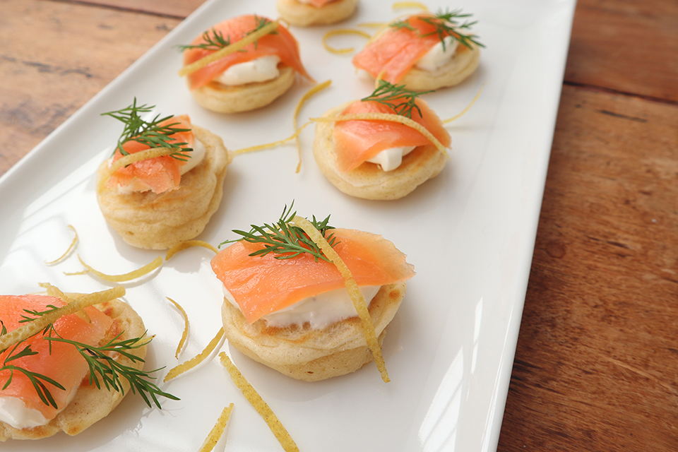 Smoked salmon bilinis on white platter