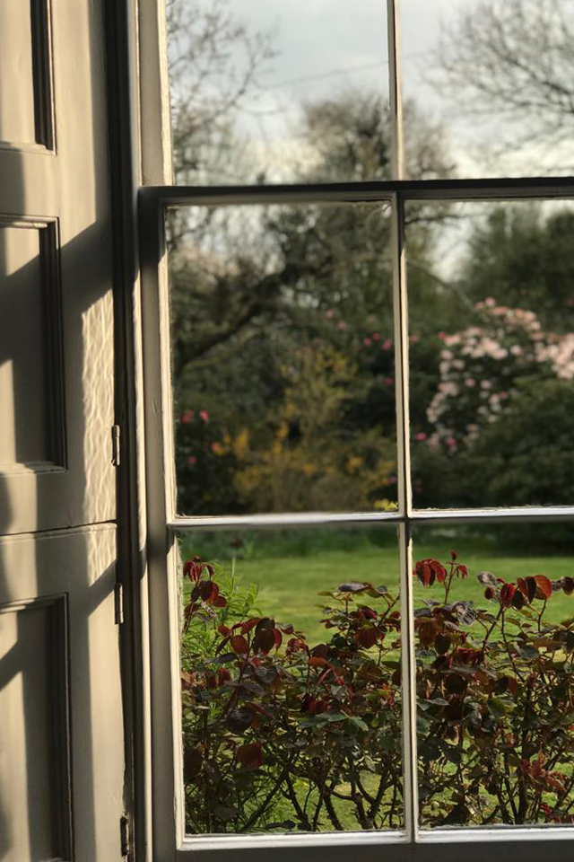 Large sash window in Georgian country house looking out towards spring garden