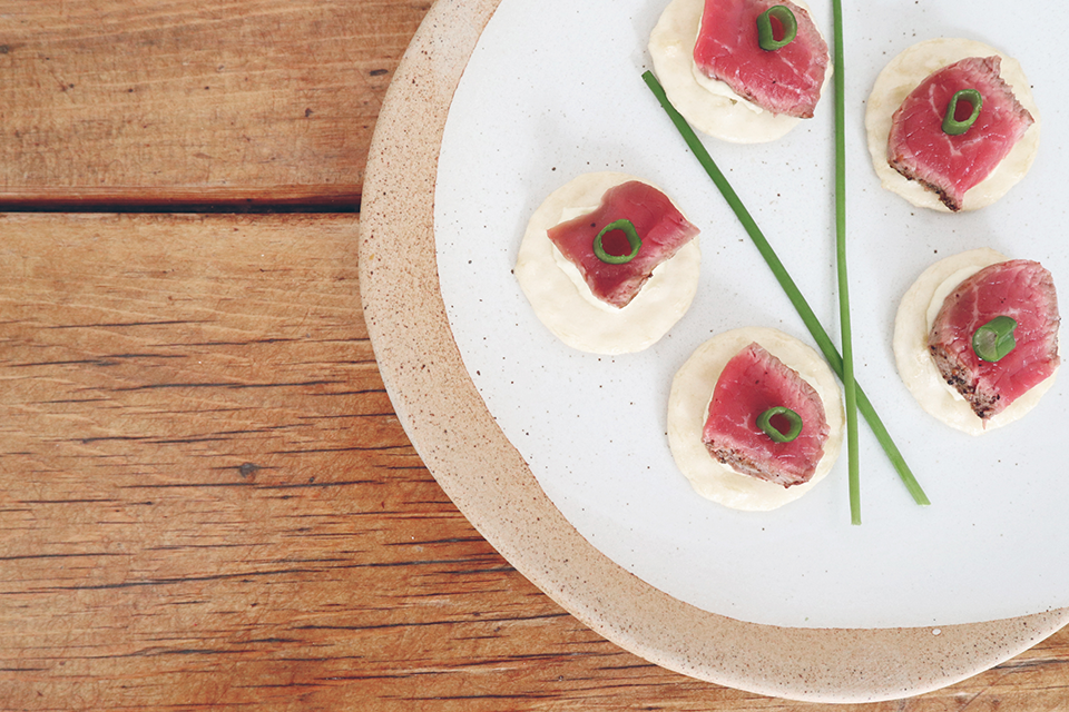 Seared beef and horseradish with chives on platter