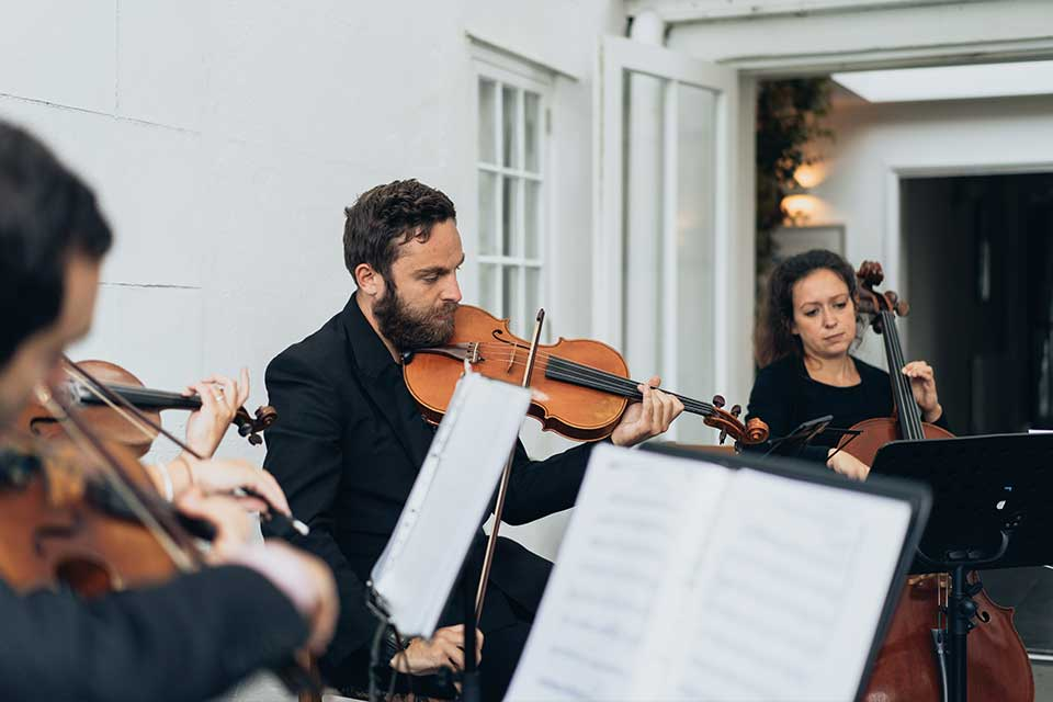 String Quartet playing on the terrace at a small wedding