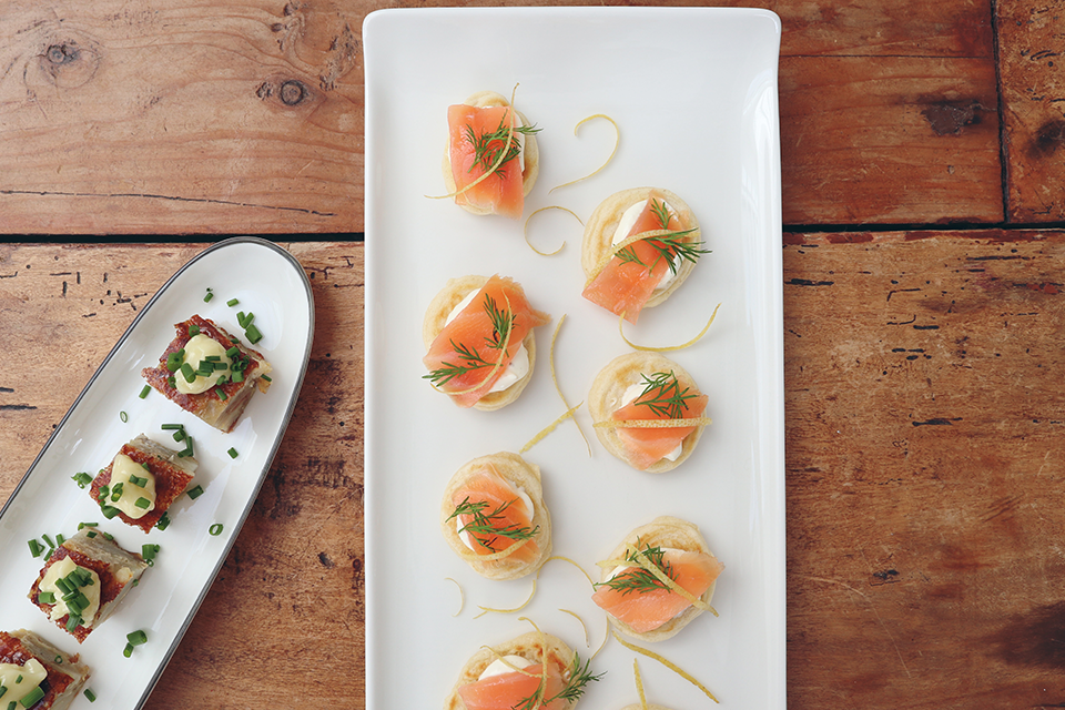 Smoked salmon blinis with green garnish on white platter