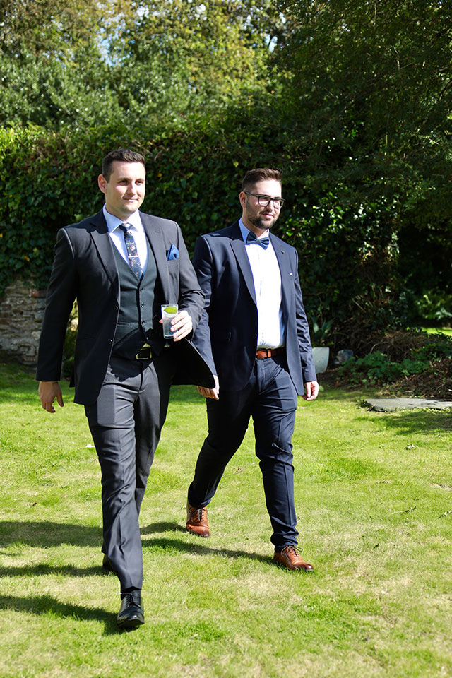 two groomsmen in navy blue suits at outdoor wedding