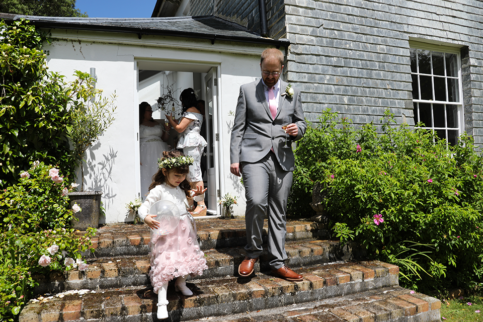 groom and flower girl walking down steps in sunshine