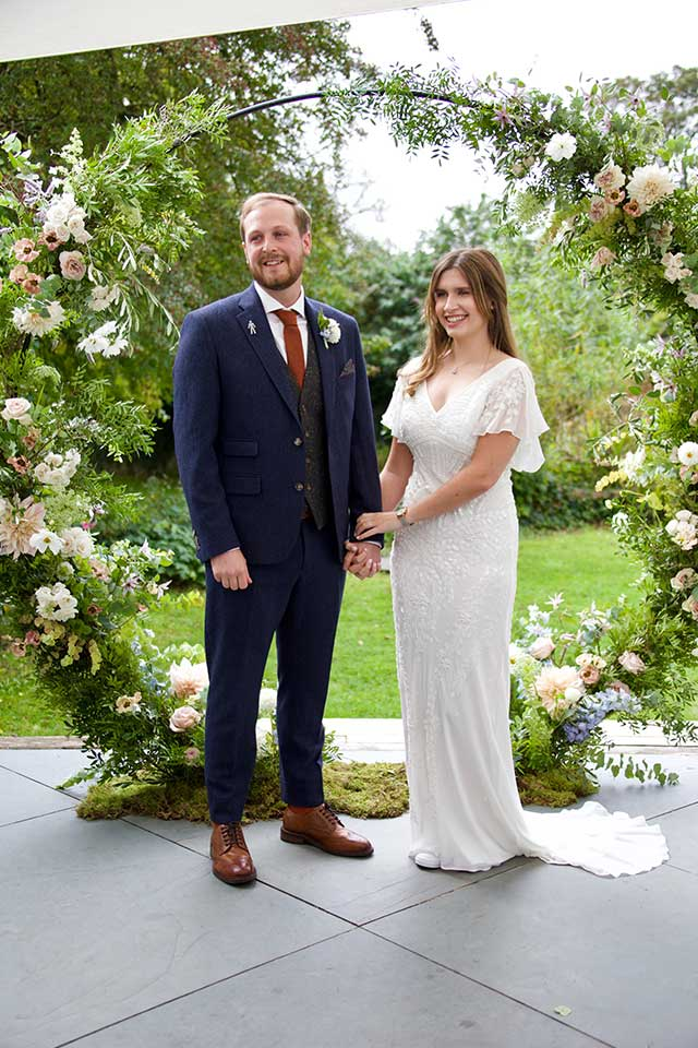 smiling bride and groom standing outside in front of floral wedding arch