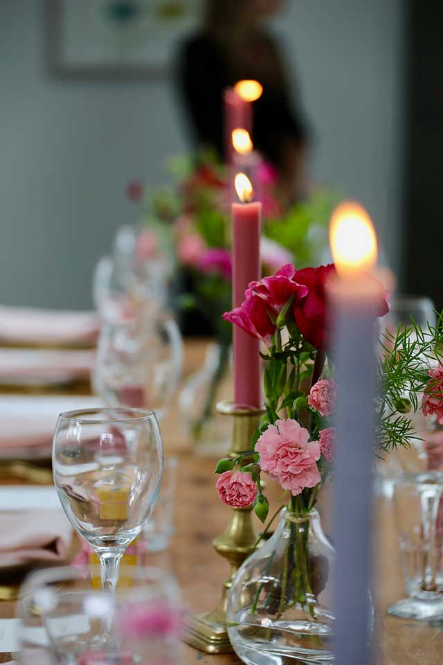 pink and purple tapered candles on wedding table