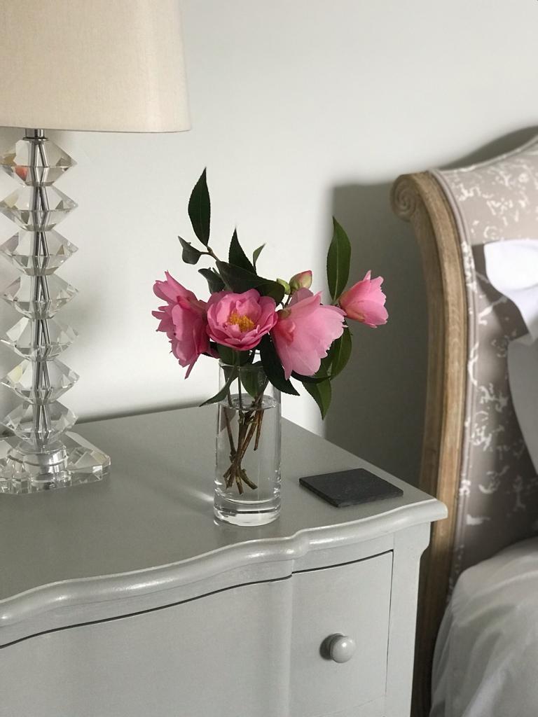 Pink camelias in glass vase in bedroom