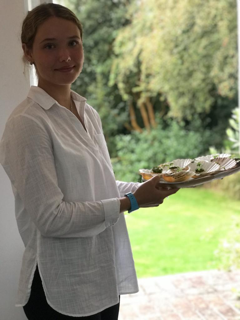 Girl wearing white shirt serving wedding canapes