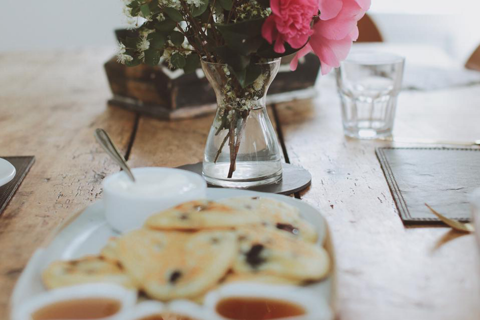 Close up blueberry pancakes on wooden table with vase of pink flowers
