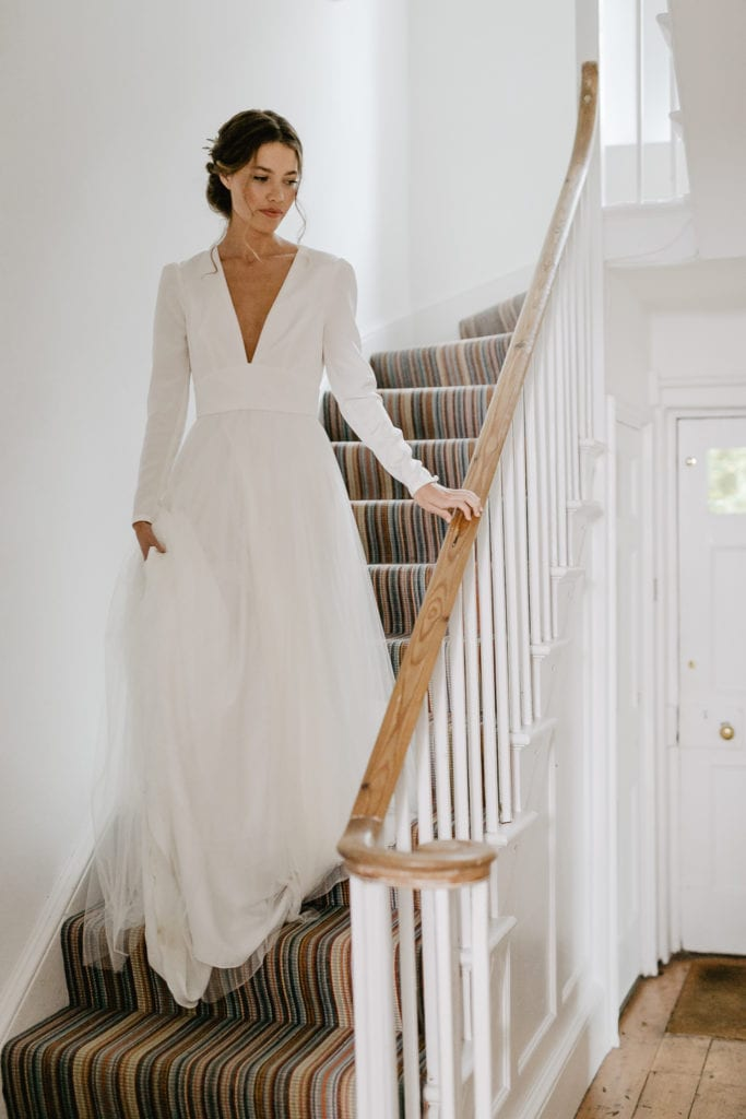 bride in wedding dress walking down staircase