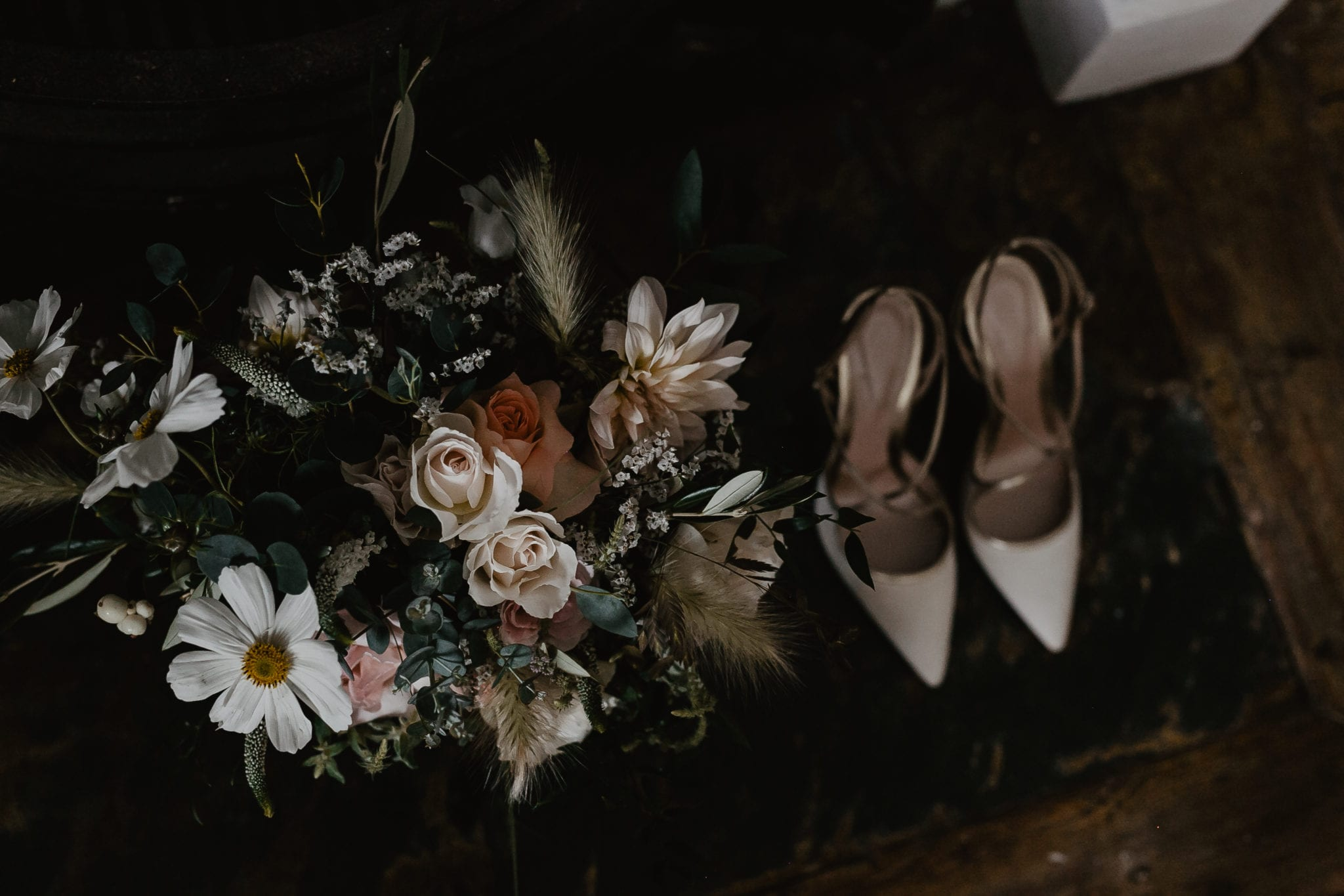 Pink and cream wedding flowers next to cream wedding shoes