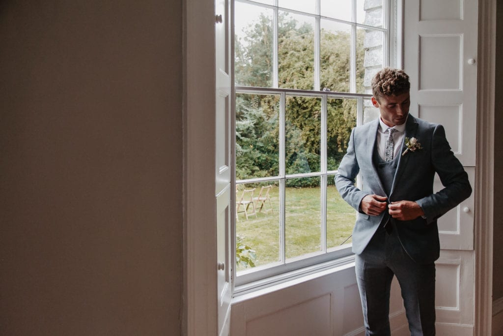 Groom stood in elegant Georgian bay window buttoning suit jacket