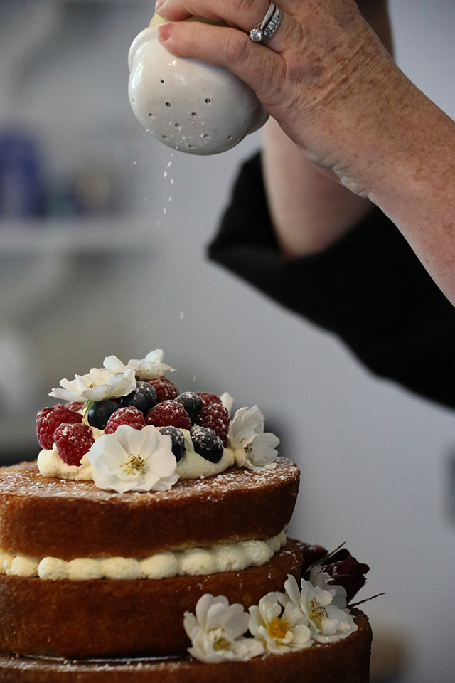 victoria sponge with cream and fresh fruit being sprinkled with icing sugar on wedding day