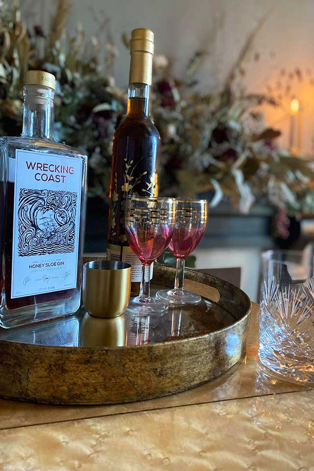gold drinks tray with vintage pink glasses, gold shot glass and Cornish Wrecking Coast gin bottle