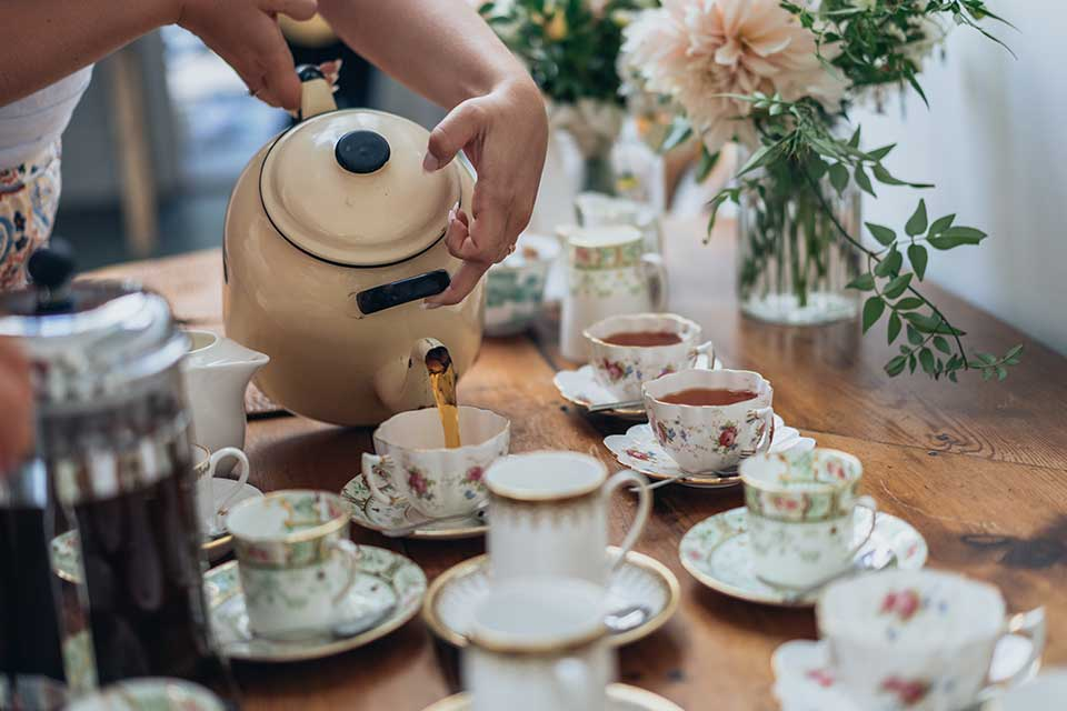 tea being poured from giant teapot into vintage china
