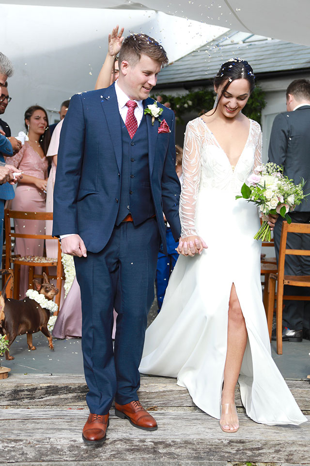 smiling bride and groom walking away from ceremony with confetti