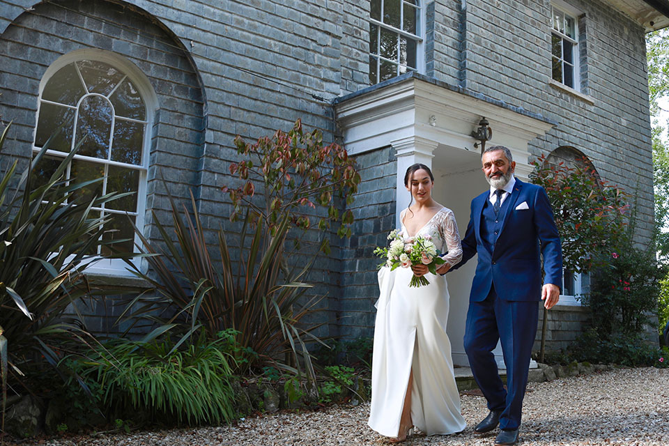 Bride and father of the bride walking to ceremony outside Georgian country house