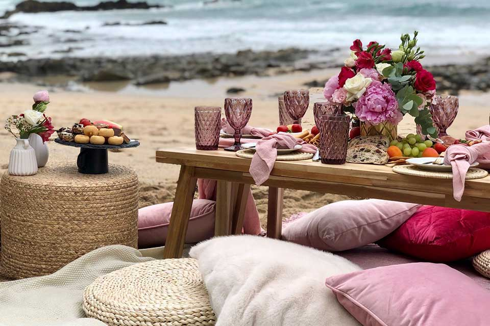 picnic setup on the beach in Cornwall with cushions and coloured glasses