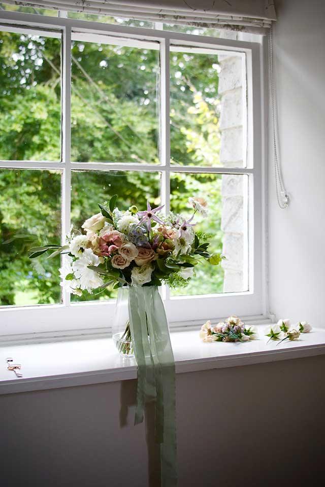 delicate blush wedding bouquet in vase on windowsill