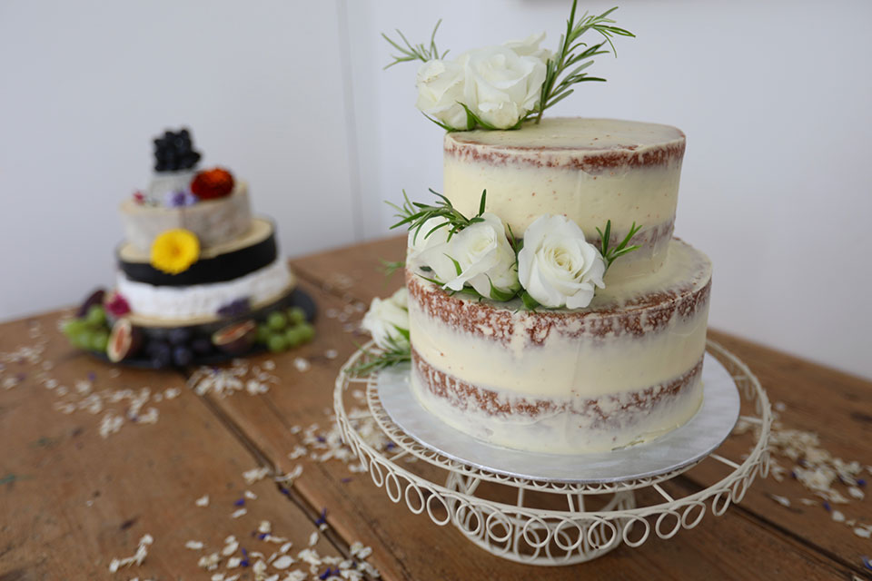 2 tiered naked wedding cake with white roses on wooden table