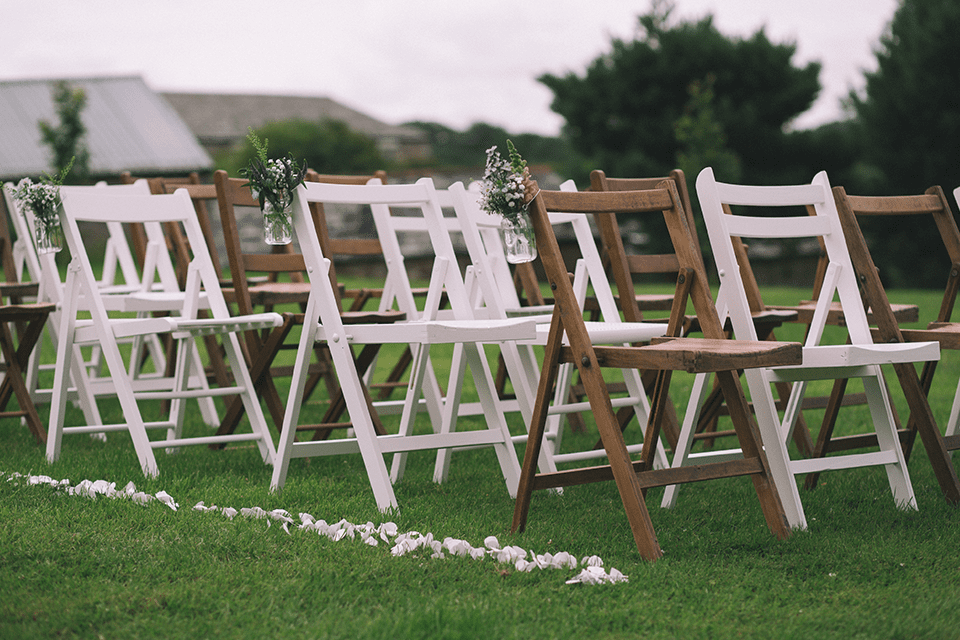 wooden white chairs set up for an outdoor wedding on green grass