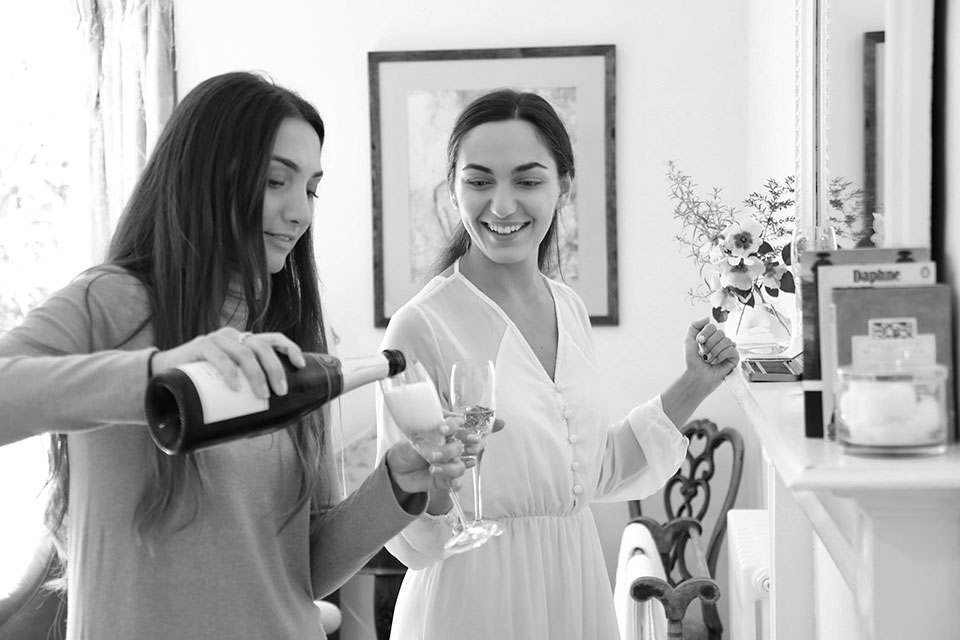bridesmaid pours champagne for bride while getting ready for wedding