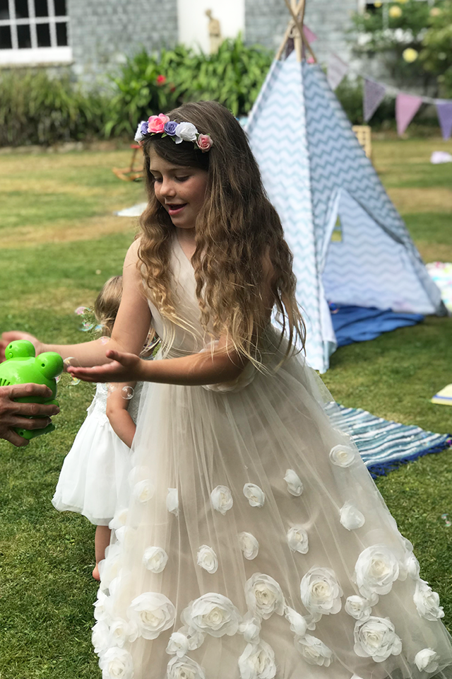 Child bridesmaid playing with bubbles at country garden wedding